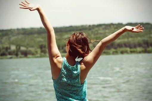 mujer de espaldas frente a un lago
