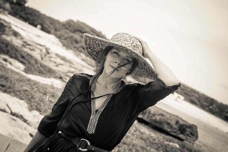 mujer con sombrero en una costa de fondo