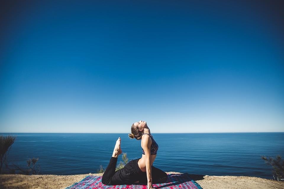 chica practicando yoga frente al mar